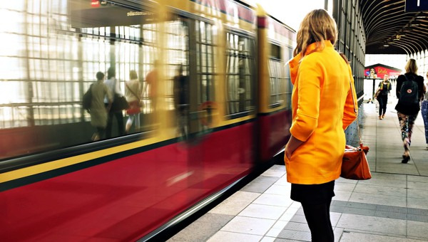 Woman in a yellow coat waiting for public transportation using ultra high density wireless